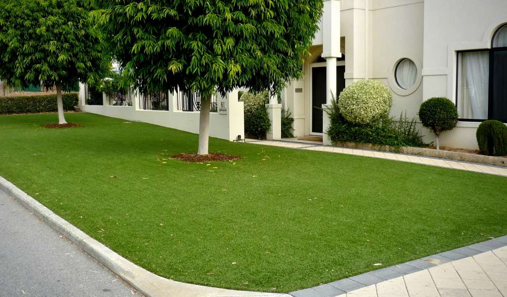 artificial lawn along the front of a house and surrounding a couple of trees