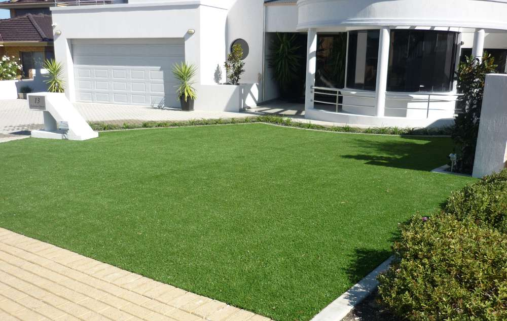 artificial lawn in frontyard of two storey white house