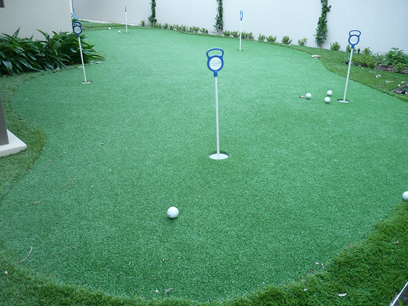 artificial turf putting green with several cups